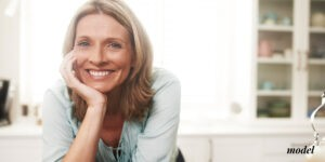 Smiling Female Leaning Over Kitchen Counter